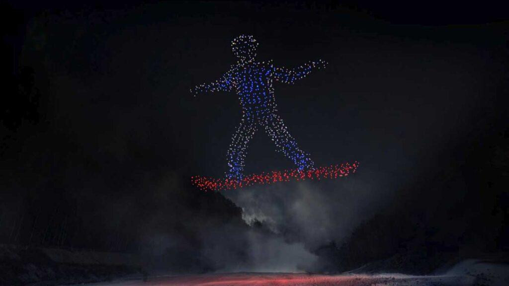 figura di uno snowboarder creata con droni luminosi